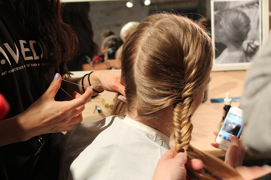 """It's simple, but it looks intricate,"" Antoinette Beenders, Aveda's global style director, said. ""It fools the eye."" The straightforward style started with a fishtail French braid on either side of the head. Once secure, Beenders pulled on the braids to fatten and texturize them before crossing them at the nape of the neck."