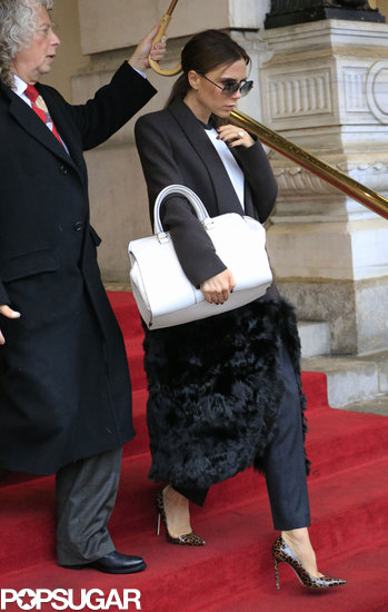 Victoria Beckham carried a large white purse.
