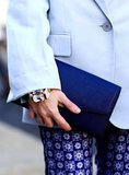 A structured dark blue clutch complements the cool water hues on this sleek outfit.