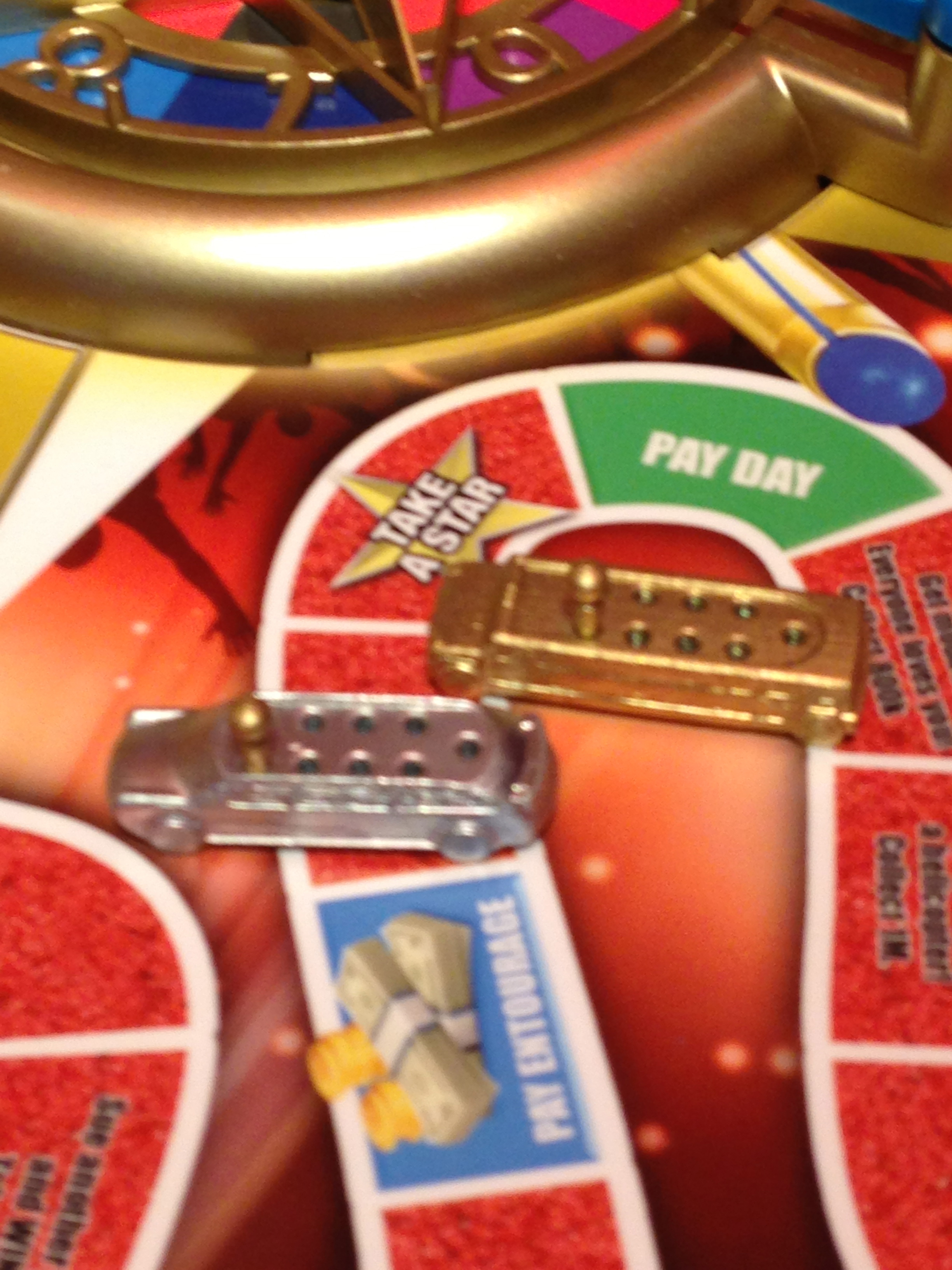 Forgot those little colorful cars — in The Game of Life Fame Edition, your play pieces are metallic stretch limos.