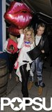 Rita Ora grabbed dinner in London with a group of friends while holding onto giant kiss balloons.