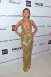 Heidi Klum wore a revealing gold dress to Elton John's Oscar party.