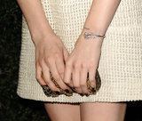 To punch up the cool quotient on her Chanel cream-colored tweed dress, Chloë accessorized with the label's Plume bracelet.