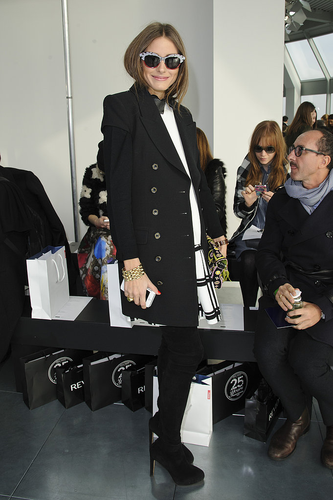 Looking every bit the trendsetter, Olivia posed in a window pane plaid Tibi dress, black coat, over-the-knee suede boots, and funky cat-eye shades at Antonio Berardi at LFW.