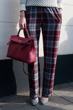 We love how this chic berry satchel popped against a pair of plaid trousers.