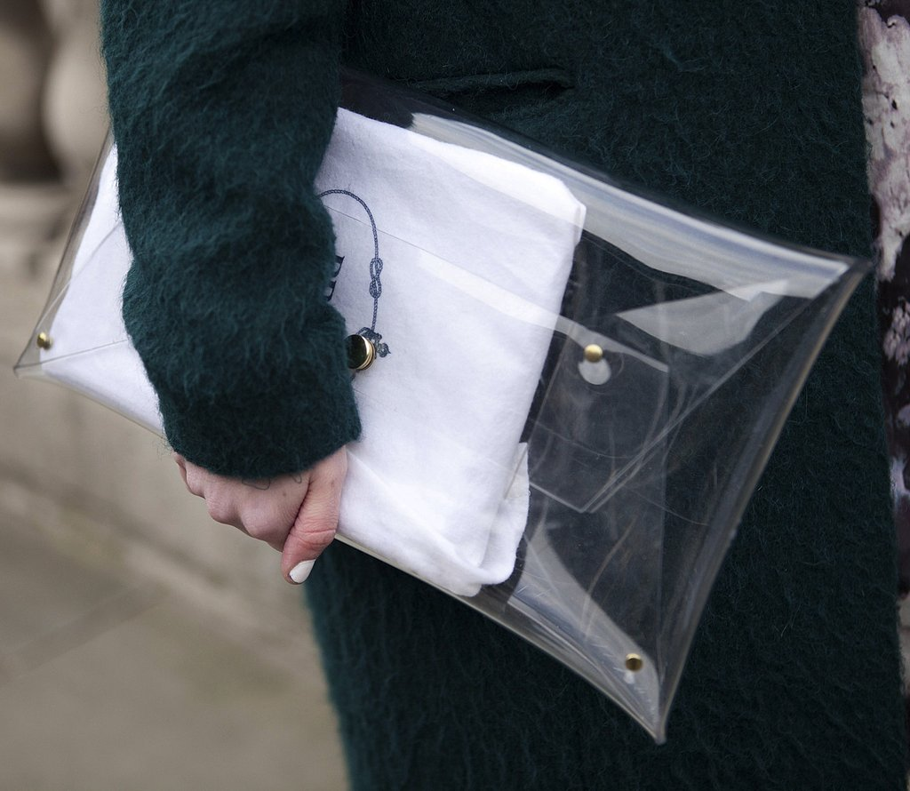 A clear Prada envelope clutch complemented a textural dark-green coat.