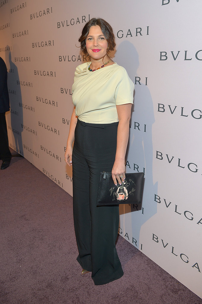 Drew Barrymore donned a silk cream and black jumpsuit paired with a bold clutch.