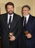 Ben Affleck and George Clooney smiled while holding their BAFTA Awards.