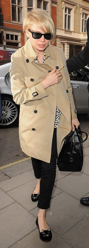 While arriving to London for more promotions, Michelle Williams was sleek in a khaki trench coat, a star-print blouse, black cropped pants, and cat flats.