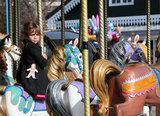Honor Warren took a seat on a horse while riding the merry-go-round.