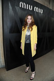 Alice Englert wore a yellow coat to Miu Miu's show.