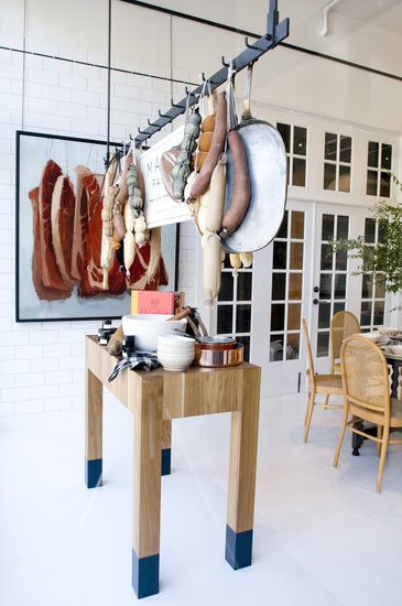 Utilize racks to hang more than just pots and pans. While you may not have ropes of sausage and dried salamis at the ready, things like potted herbs and sacks of garlic would achieve the same rustic culinary feel.