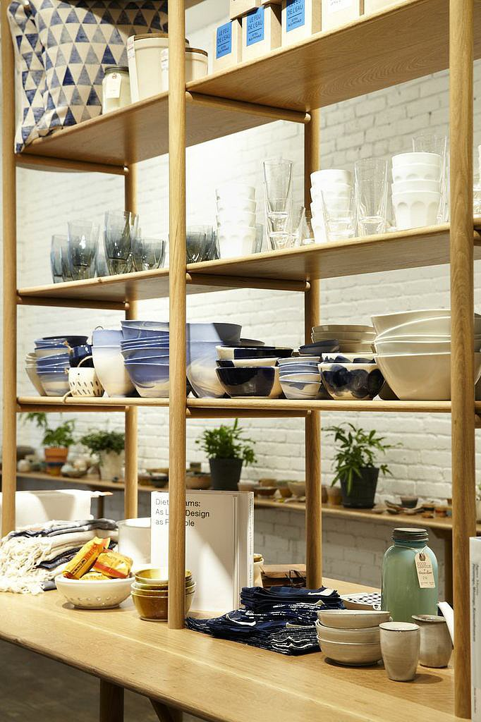 Simple wooden shelving displays a variety of housewares.