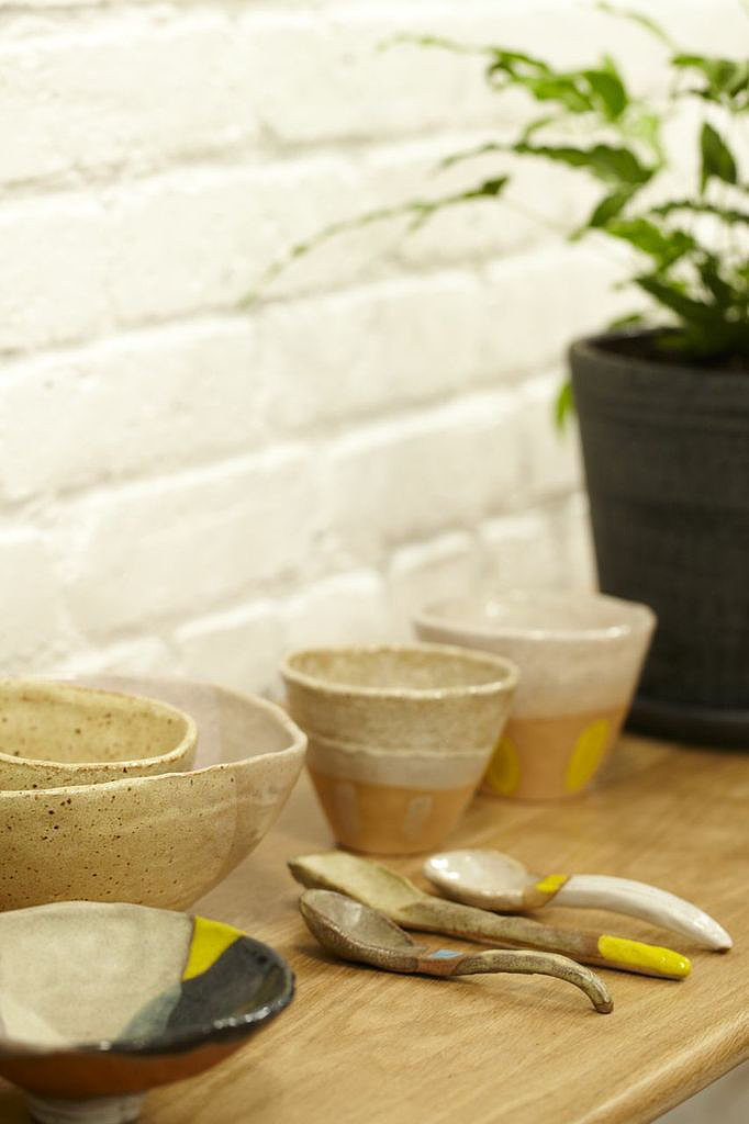 Ceramic bowls and spoons are displayed against a painted brick wall.