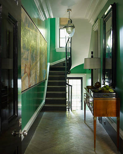 This captivating entryway uses kelly-green walls and gold finishes to set the tone of the entire house.  Source: Elle Decor