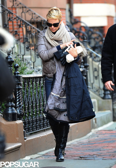 Charlize Theron carried her jacket, gloves, and phone.