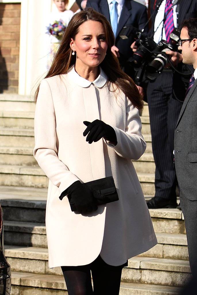 Kate Middleton wore a collared white jacket with black gloves.