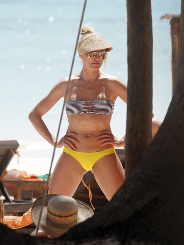 During a March A-list girls' vacation in Mexico with Reese Witherspoon and Drew Barrymore, Cameron Diaz showed off her toned body in a striped bandeau bikini top, yellow bottoms, a straw visor, and mirrored aviator sunglasses.