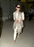 Emilia Clarke's travel style included white cropped trousers, a white blazer, a printed scarf, and off-white flats.