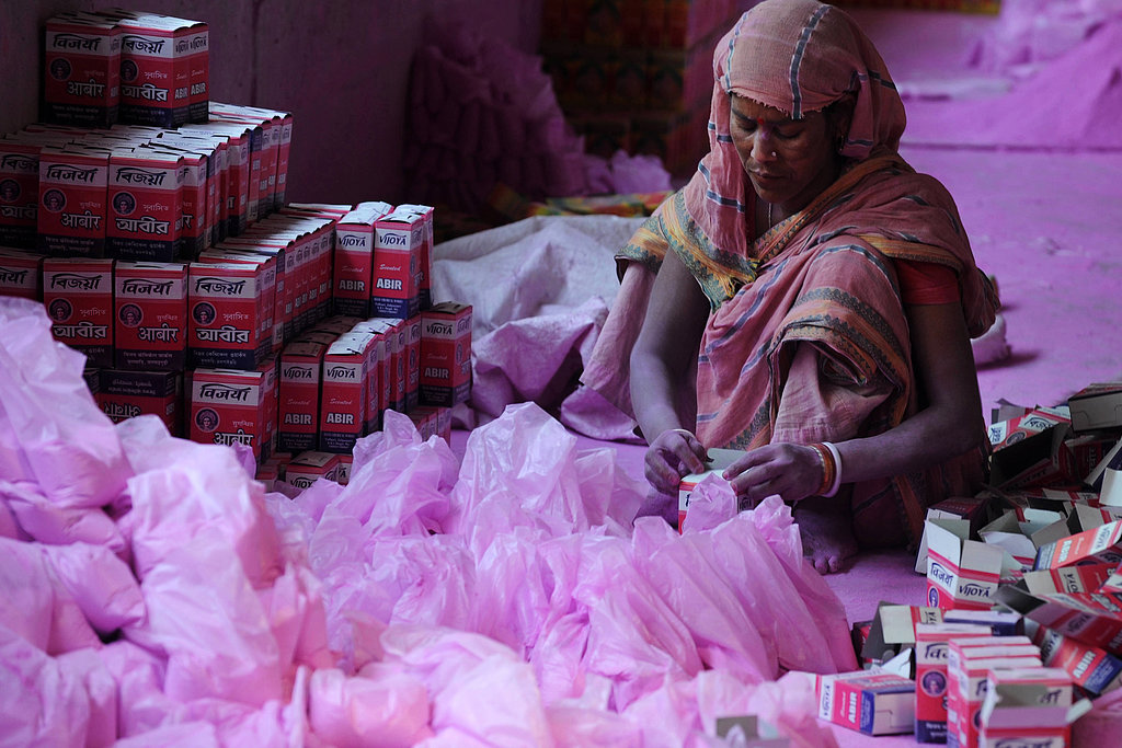 A laborer packed colored powder, known as gulal, to be used during Holi, on the outskirts of Siliguri, India.
