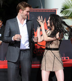 Robert Pattinson and Kristen Stewart played around after they left their handprints in cement at their hand and footprint ceremony in LA in November 2011.