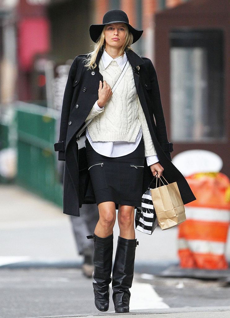 Karolina Kurkova layered up in a white collared blouse, an ivory cable-knit sweater, a black coat, and a black zippered skirt during a stroll in NYC, then added a floppy hat, a white crossbody bag, and black leather boots for an even more stylish finish.