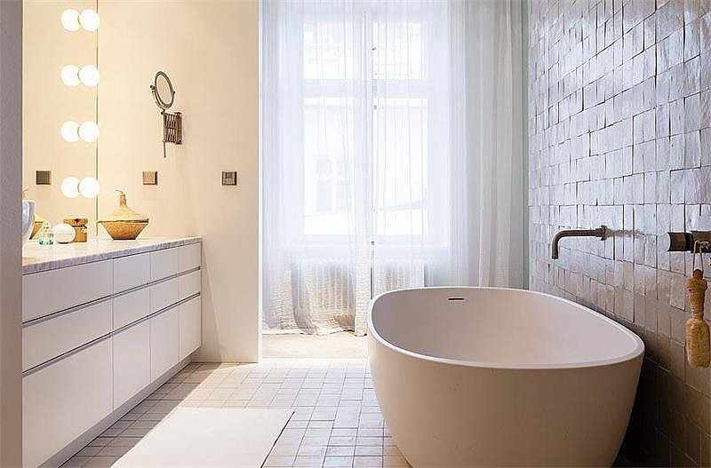 The bathroom features neutral tiles and a smooth, minimalist bathtub. Source: Sotheby's