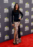 Zoe Saldana fused feminine with sexy in a floral maxi skirt by Givenchy, complete with a thigh-high slit. She finished with black ankle-strap peep-toes by Jimmy Choo.