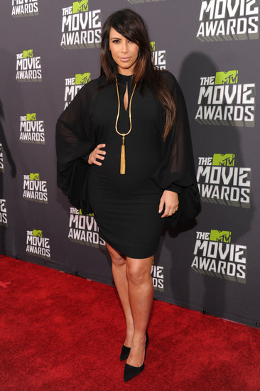 Kim Kardashian covered up in a little black dress with sheer sleeves, then added a gold tassel necklace for a pop of shine.