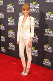Bella Thorne chose a slim pantsuit in an off-white color, then added feminine touches via metallic pumps and colorful jewelry at the MTV Movie Awards.
