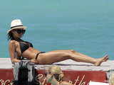 Nicole Richie lounged in St. Barts wearing a black triangle bikini, House of Harlow cat-eye sunglasses, and a crisp white fedora.