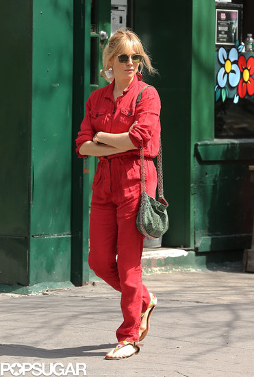 Sienna Miller carried a green purse.