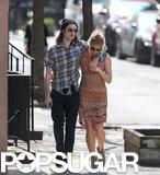 Tom Sturridge and Sienna Miller cuddled up while walking through NYC on Wednesday.