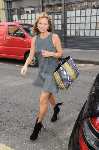Kate Moss ditched her signature skinny jeans for a more feminine gray suede dress with a ruffle hem. She then added a colorful snakeskin tote bag and black booties to her feminine London style.