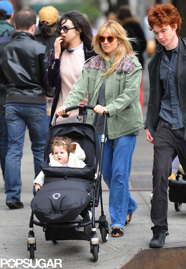 Sienna Miller strolled NYC with her daughter Marlowe wearing an army green jacket with printed shoulder detail, wide-leg jeans, leopard loafers, and round orange sunglasses.