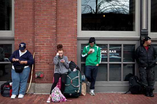 Stranded travelers stood outside Boston's South Station after it was shut down following the early-morning shootings in Cambridge and Watertown.