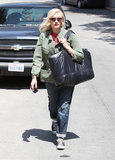 Gwen Stefani exuded boyish appeal in her army jacket, which she paired up with ripped boyfriend jeans, a red tee, Converse sneakers, a black plastic Chanel tote bag, and clear sunglasses in LA.