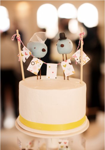 Even supersimple cakes can bring on the fun factor. Just look at this quirky husband-and-wife topper adorning a white-and-yellow cake.  Photo by Studio222 Photography via Wedding Chicks