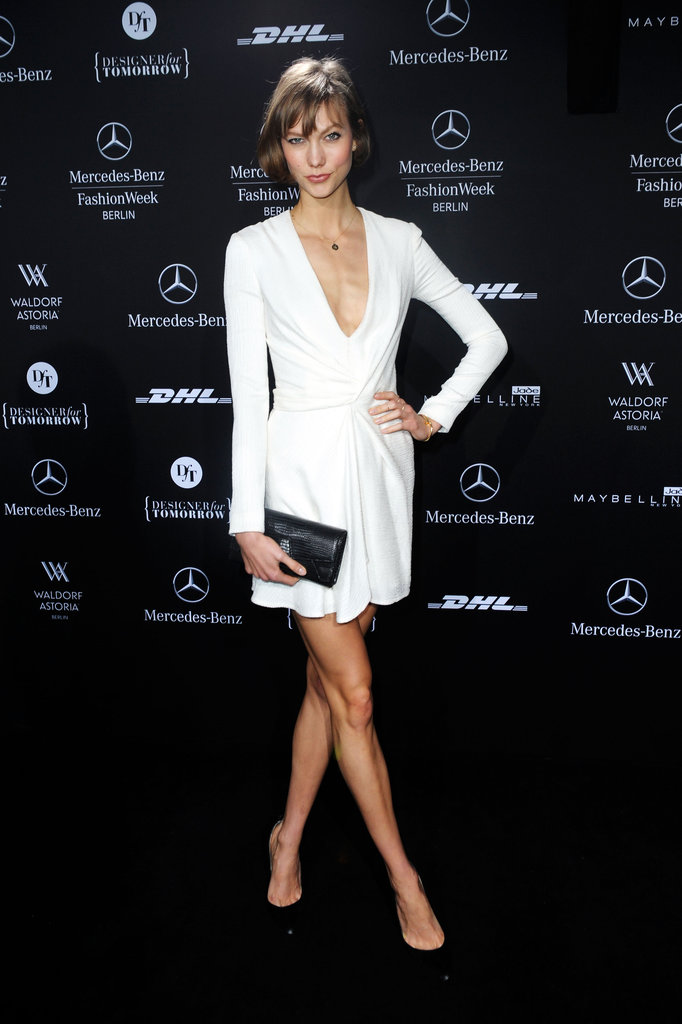 Karlie Kloss kept her sleeves long but neckline plunging in a white minidress at an event in Berlin. Her black add-ons served as chic contrasts.