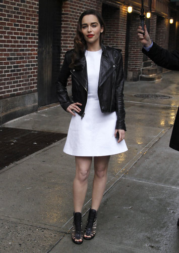 While out in NYC, Emilia Clarke's little white dress took on a tough-chick attitude, thanks to her black leather biker jacket and black caged booties.