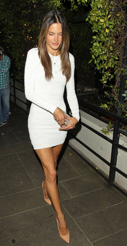 Alessandra Ambrosio put her long legs on display in a little white long-sleeved dress, then kept up the elongating effect via nude pointy pumps.