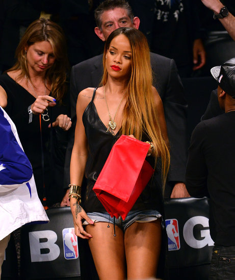 When Rihanna stood up, she showed off her denim minishorts and red foldover clutch.