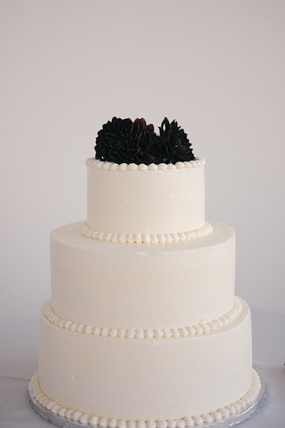 Here, less is more: edged with a beaded detail and topped with a black flower, this cake is sleek and sophisticated.  Photo by Erica Rose Photography via Style Me Pretty