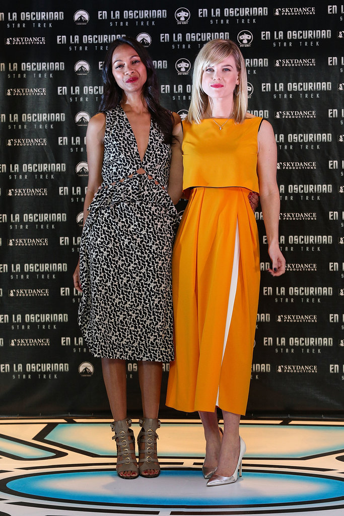 At the Mexico City photocall for Star Trek Into Darkness, Zoe Saldana matched her Bottega Veneta geometric-print dress with contrasting tough cutout Salvatore Ferragamo booties, while her costar Alice Eve brightened the room in an orange tiered dress and silver metallic pumps.