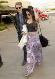 Vanessa Hudgens gave us more of her gypsy-inspired aesthetic in a purple printed maxi skirt, a black crop top, a black Western hat, and a fringe bag.
