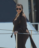 Kim Kardashian showed off her baby bump in a brown dress while relaxing on a Greek vacation with her family in April 2013.