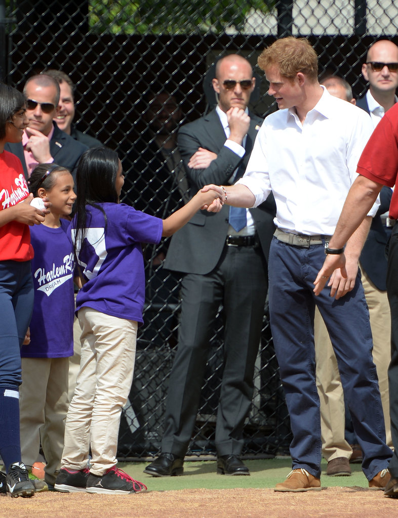 Prince Harry shook hands with a young girl in Harlem on Thursday.
