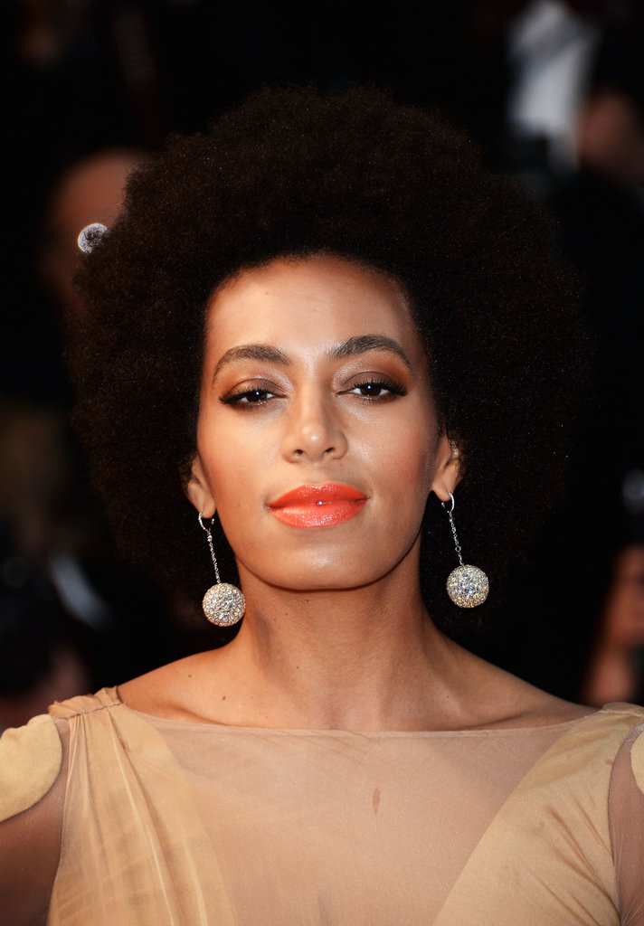 While attending the Great Gatsby premiere in Cannes, Solange Knowles wore a bright tangerine lip color to brighten up her camel-colored gown and signature Afro.
