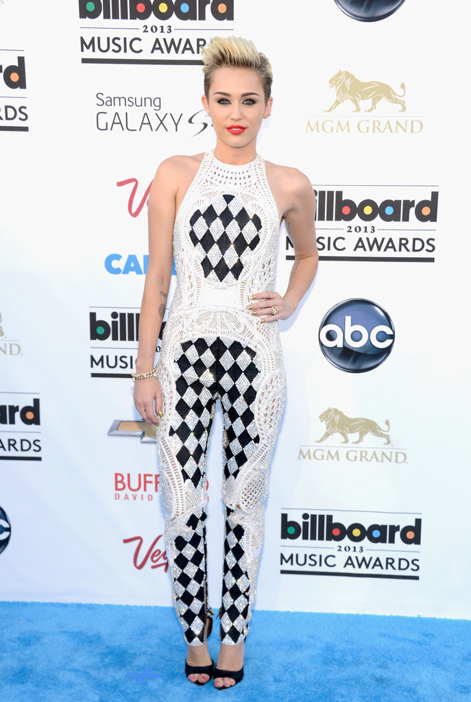 Miley Cyrus showed off her fit figure in a Balmain jumpsuit featuring a black checker-like print. She finished it all off with black Givenchy sandals and a bold red lip.