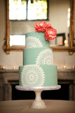 Pairing citrus-colored flowers against this mint-and-white cake is pretty genius (and ultrafeminine), if you ask us.   Photo by Laura Ashbrook Photography via Style Me Pretty